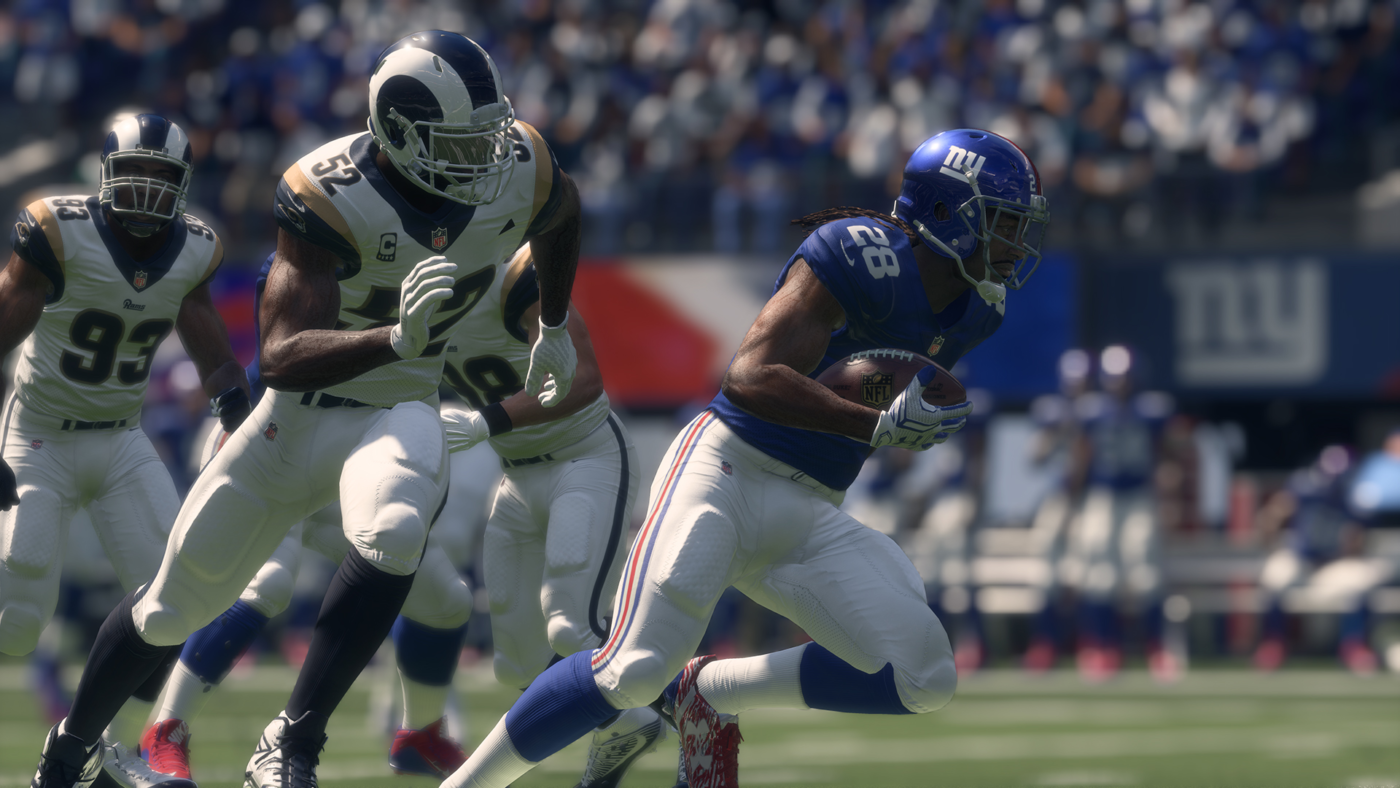 Madden NFL 18 Football player running with the ball in hand while being chased by opponents while crowd watches on in the background